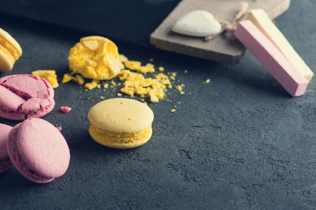 Closeup of pink macaroons on black concrete background Premium Photo