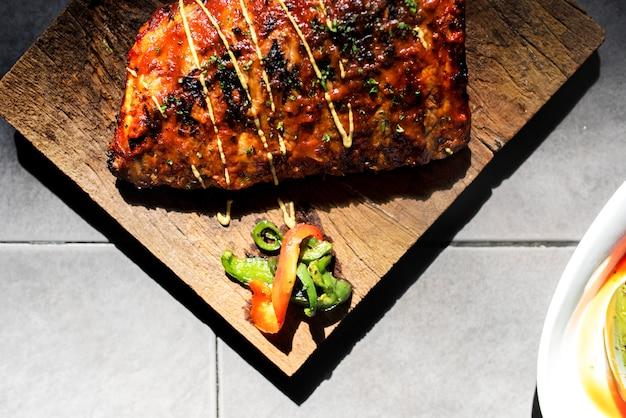 Closeup of pork ribs steak on wooden board food styling Free Photo