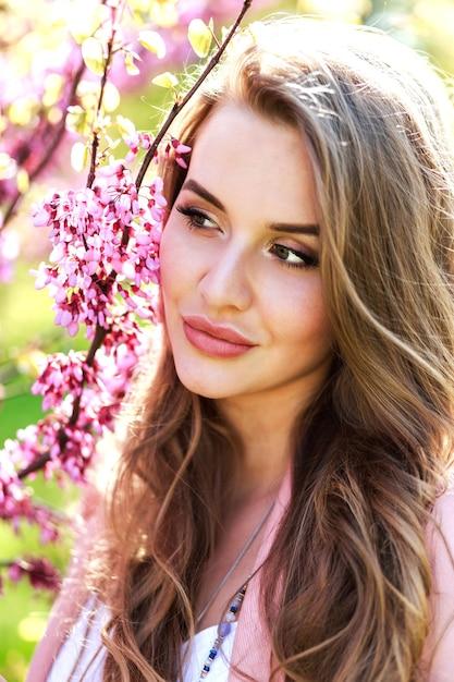 Closeup ritratto incredibile giovane donna allegra con i capelli lunghi alla luce del sole all'aperto Foto Gratuite