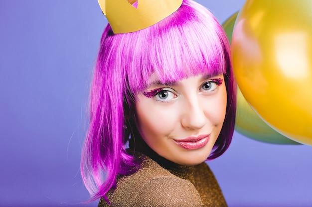 Closeup ritratto incredibile gioiosa giovane donna con capelli viola tagliati, corona d'oro e palloncini che celebrano il carnevale, festa di capodanno. sorriso affascinante, trucco con orpelli, felicità. Foto Gratuite