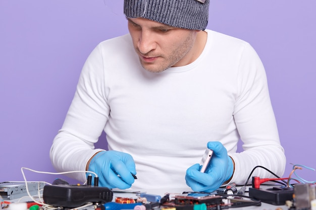 Closeup portrait of attentive well skilled electronic engineer doing repair Free Photo