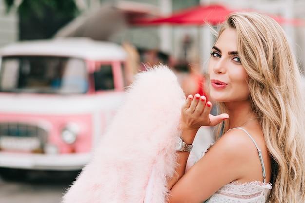 レトロな車の背景に手でピンクの毛皮を盗んだポートレート、クローズアップの魅力的な女の子。彼女はカメラにキスを送っています。 無料写真