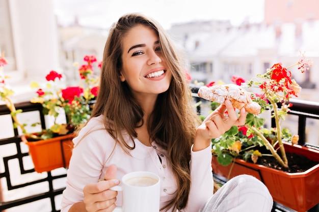 Bella ragazza del ritratto del primo piano con capelli lunghi che fa colazione sul balcone la mattina in città. tiene una tazza, un croissant, sorridendo. Foto Gratuite