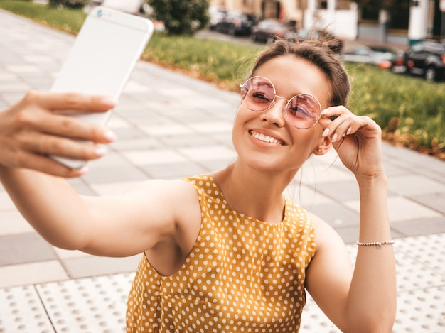 Closeup portrait of beautiful smiling brunette girl in summer hipster yellow dress. model taking selfie on smartphone.woman making photos in warm sunny day in the street in sunglasses Free Photo
