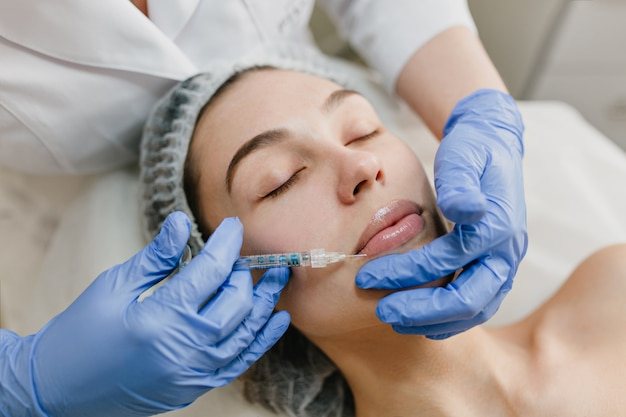 Closeup portrait of beautiful woman during cosmetology therapy in beauty salon. botox, lips, injecting, professional  procedures, lifting, rejuvenation, modern devices, healthcare Free Photo
