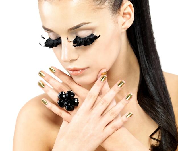 Closeup ritratto della bella donna con trucco ciglia finte nere lunghe e unghie d'oro. Foto Gratuite