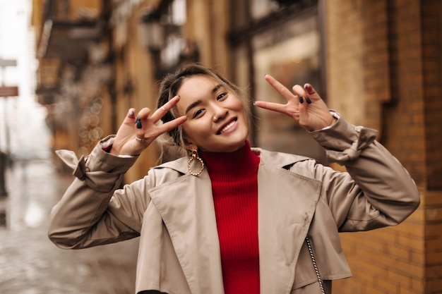 Closeup portrait of cute asian woman in red top and beige trench coat smiling and showing peace signs on wall of beautiful building Free Photo