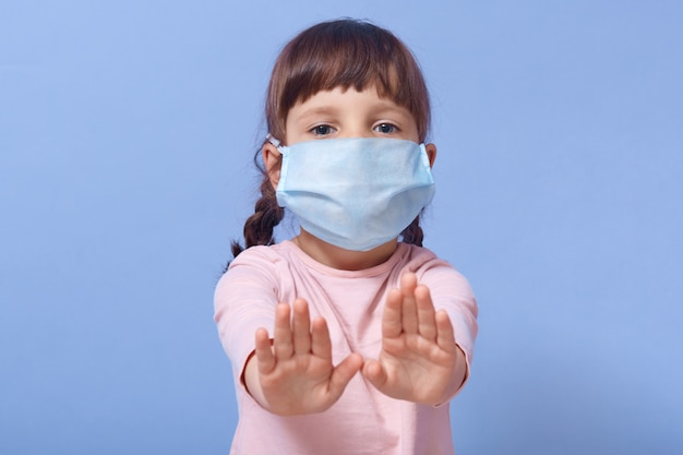Closeup portrait of cute child wearing casual shirt and medical mask, female kid showing stop gesture with both palms Free Photo