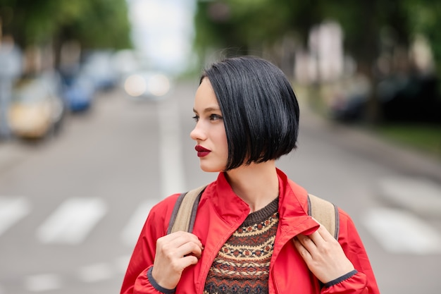 Closeup portrait of cute pensive girl in red jacket and backpack on the street Premium Photo