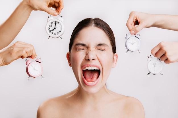 Closeup ritratto di emotivamente urlando giovane donna contro il muro bianco con sveglie. Foto Gratuite