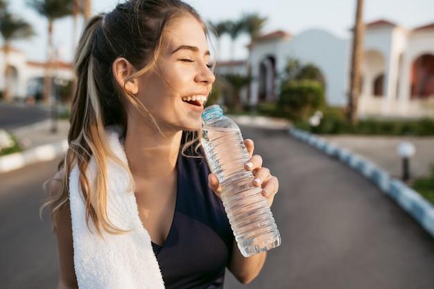 Il ritratto del primo piano ha eccitato la giovane donna felice che sorride con gli occhi chiusi al sole con la bottiglia di acqua. attraente sportiva, godersi l'estate, la formazione, il lavoro, la felicità. Foto Gratuite