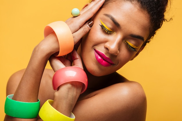 Closeup portrait of fashion afro american woman with bright makeup and multicolour accessories holding hands at face, isolated over yellow wall Free Photo