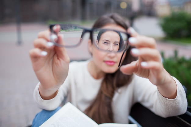 Closeup portrait of female with eyeglasses in hand. Premium Photo
