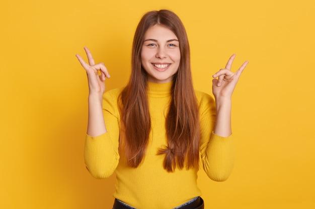 Closeup portrait of happy smiling woman showing rock sign Premium Photo