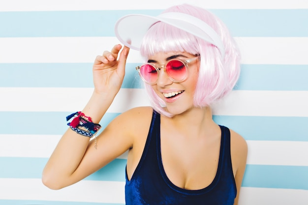 Closeup portrait hot summer beach time of fashionable woman in pink sunglasses, with cut pink hairstyle having fun on striped wall. stylish sexy look, cheerful mood, smiling with closed eyes. Free Photo