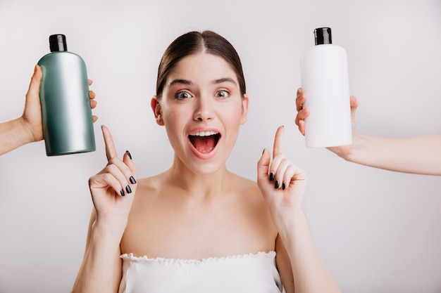 Closeup portrait of joyful girl posing without makeup on white wall. woman chose which shampoo is best to use. Free Photo