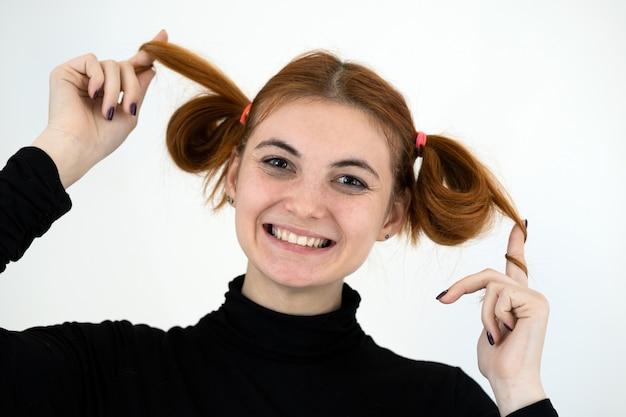 Портрет крупного плана смешной рыжей девочки-подростка с детской прической, счастливо улыбаясь, изолированной на белом фоне. Premium Фотографии