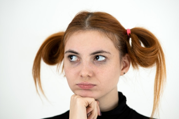 Портрет крупного плана грустной рыжей девочки-подростка с детской прической, смотрящей обиженной. Premium Фотографии