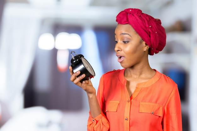 Макрофотография портрет подчеркнул женщина холдинг, с тревогой глядя на часы Premium Фотографии