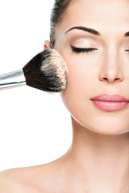 化粧ブラシを使用して顔にドライ化粧品の色調のファンデーションを適用する女性のクローズアップの肖像画。 無料写真