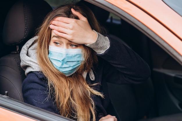 車の中で医療マスクの女性のポートレート、クローズアップ。コロナウイルスエピデミック。 sars-cov-2。 covid-19を停止します。 Premium写真