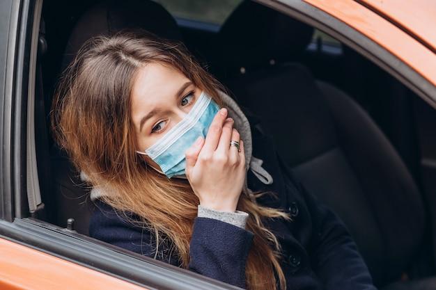 路上で医療用マスクを着た女性のポートレート、クローズアップ、コロナウイルスの流行。女性は自己分離のルールに違反しました。 sars-cov-2。 covid-19から身を守ってください。 Premium写真