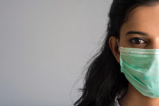 Портрет крупного плана доктора молодой девушки или женщины нося медицинскую или хирургическую маску Premium Фотографии