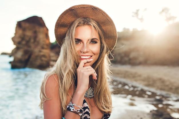 Крупным планом портрет привлекательной блондинки с длинными волосами, позирует на скалистом пляже на фоне заката. она держит палец на губах и улыбается в камеру. Бесплатные Фотографии