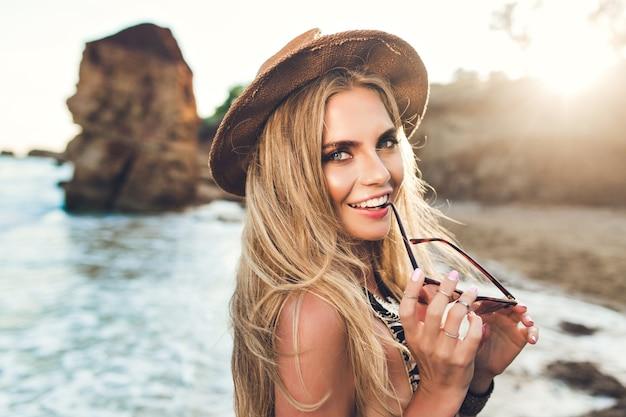 Портрет крупного плана привлекательной белокурой девушки с длинными волосами, позирующими на скалистом пляже. sона держит солнцезащитные очки и улыбается в камеру. Бесплатные Фотографии