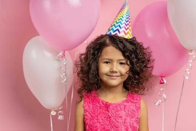 축제 옷, 생일 모자, 공기 Baloons 가운데 서 입고 행복 긍정적 인 작은 아이의 근접 촬영 초상화. 어린이, 휴가 및 축하 개념. 프리미엄 사진