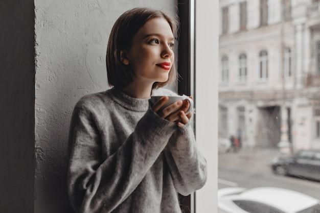 窓の近くでお茶を楽しんでいる赤い口紅と灰色のウールのセーターの女性のクローズアップの肖像画。 無料写真