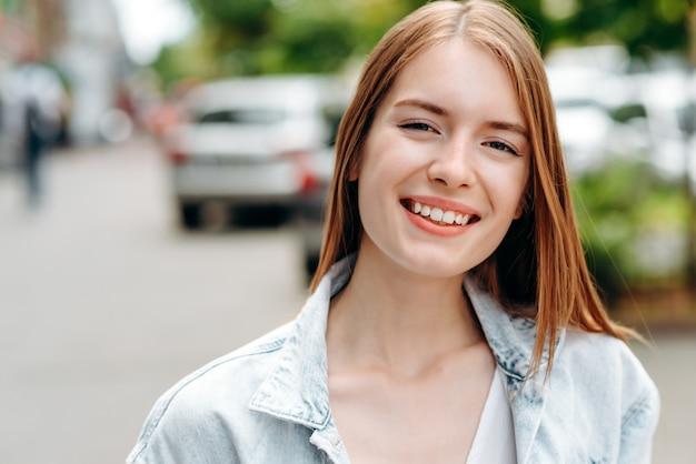 Портрет крупного плана усмехаясь женщины красно-волос стоя напольной Premium Фотографии
