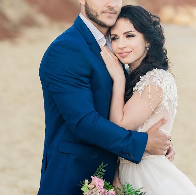 古い大聖堂でポーズをとる花束と結婚式の若い新郎新婦のクローズアップの肖像画。結婚式の日にキスする新婚旅行のカップル、恋に幸せなカップル、結婚式のキス Premium写真