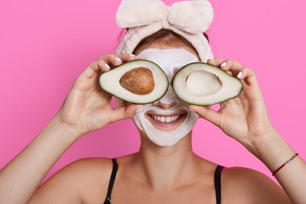 Портрет крупного плана женщины 20s с идеальной кожей, держащей авокадо против ее глаз, изолированных на розовом фоне, здравоохранении, косметических процедурах дома. Бесплатные Фотографии