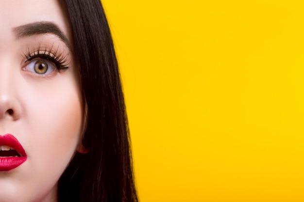 Крупным планом портрет удивленной женщины с красными губами на желтой стене Premium Фотографии