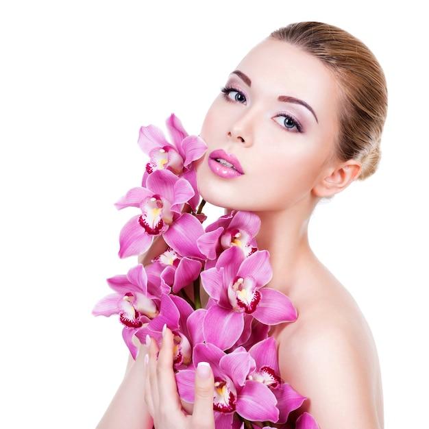 Портрет крупного плана молодой красивой женщины со здоровой чистой кожей лица. довольно взрослая девушка с цветком у лица. - изолированные на белом фоне Бесплатные Фотографии