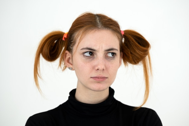 Closeup portrait of a sad redhead teenage girl with childish hairstyle looking offended isolated on white backround. Premium Photo
