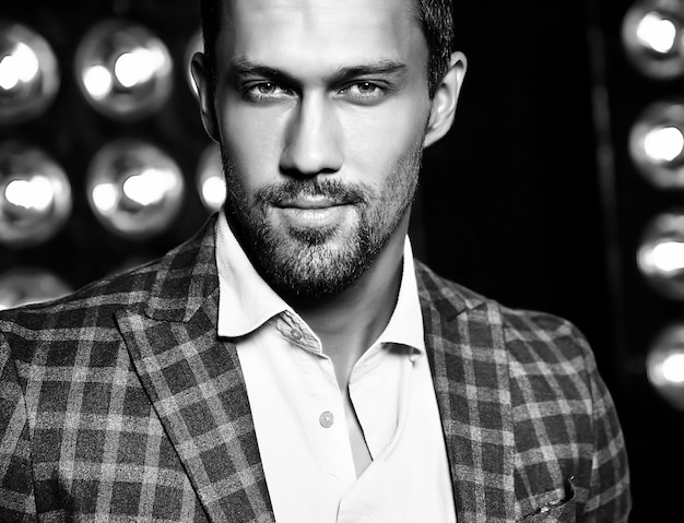 Closeup portrait of sexy handsome fashion male model man dressed in elegant suit on black studio lights background Free Photo