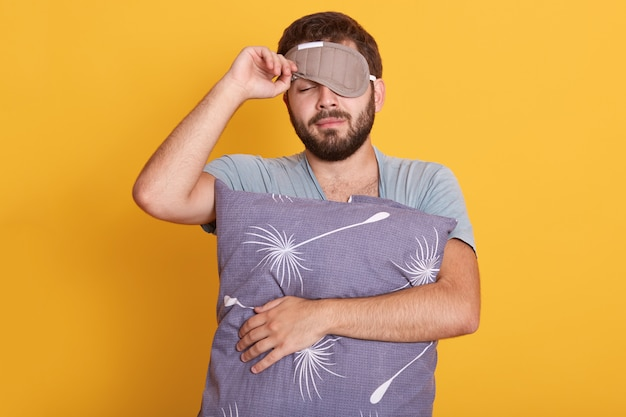Closeup portrait of sleepy man with blindfold on eyes, holding pillow in hands, opens sleeping mask, keeping eyes closed Free Photo