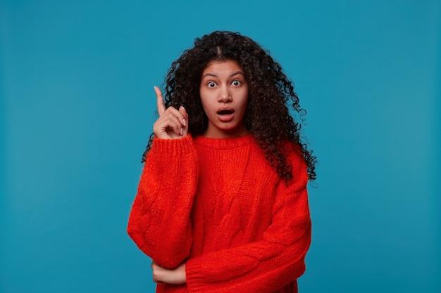 Портрет крупным планом удивил молодую кудрявую женщину, указывая указательным пальцем вверх и держа рот открытым, изолированную синюю стену Бесплатные Фотографии