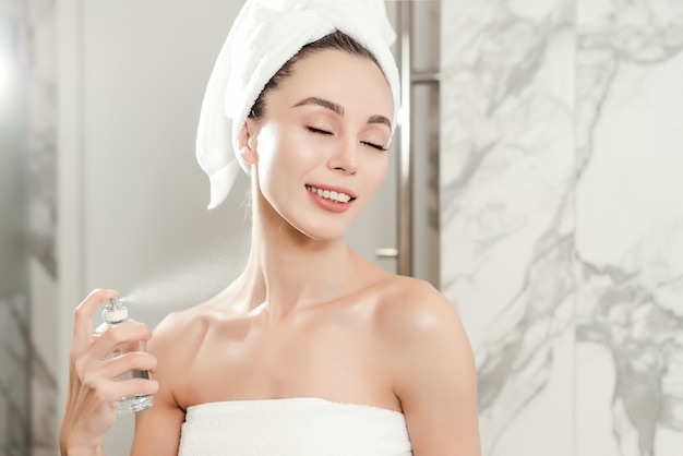 Closeup portrait with perfume spraying on the neck of young beautiful woman wrapped in towels in the bathroom.  beauty makeup and skincare concept Premium Photo