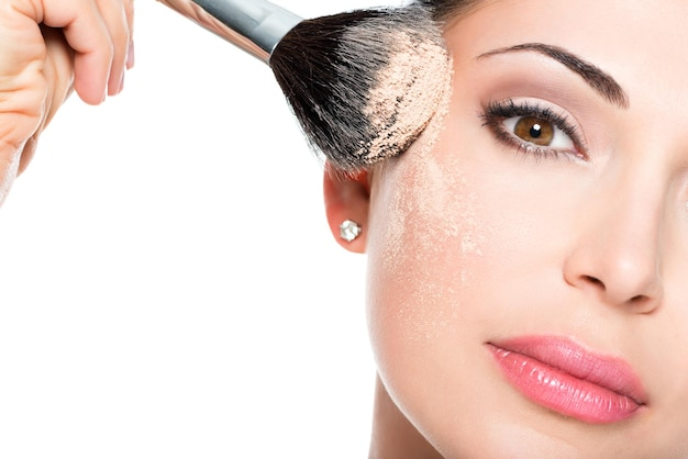 Closeup portrait of a woman  applying dry cosmetic tonal foundation  on the face using makeup brush. Free Photo