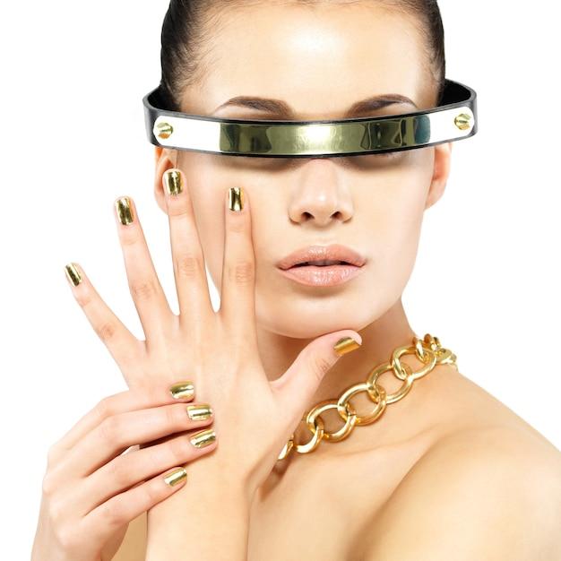 Closeup ritratto di donna con chiodi d'oro e catena d'oro sul collo Foto Gratuite