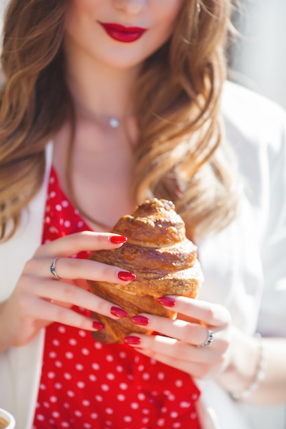 Closeup portrait of young beautiful woman eating croissant.  french girl. Premium Photo