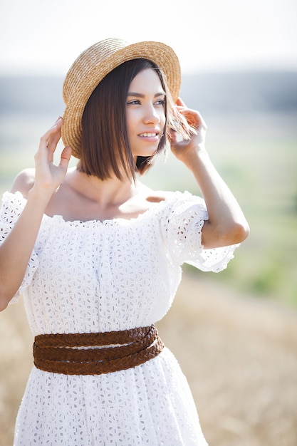 Closeup portrait of young beautiful woman outdoors on the meadow. female in the hat on summertime. lady in white dress. Premium Photo