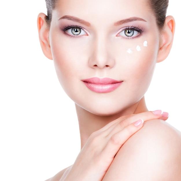 Closeup ritratto di giovane donna che applica la crema sul suo bel viso - su un muro bianco. Foto Gratuite