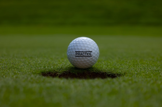 Closeup of a practice text written on a golf ball on the lawn under the sunlight Free Photo