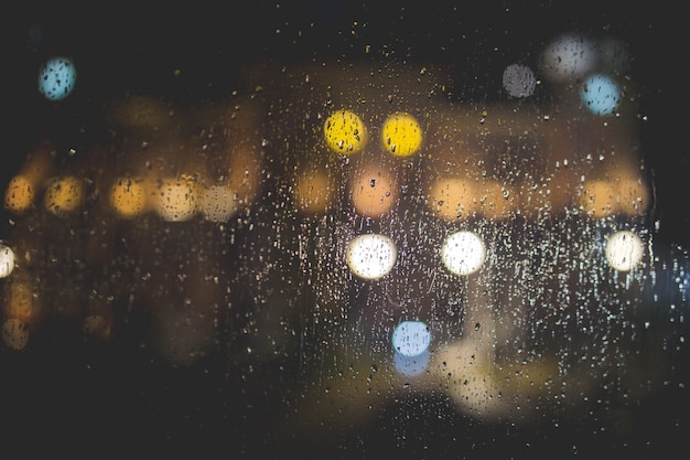 Closeup of raindrops on a clear glass window with blurred lights Free Photo