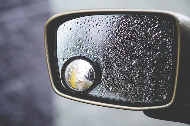 Closeup of a rearview mirror covered in raindrops under sunlight Free Photo