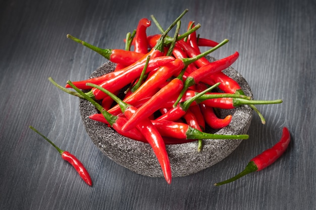 Closeup on red hot chili peppers over dark wooden table Premium Photo